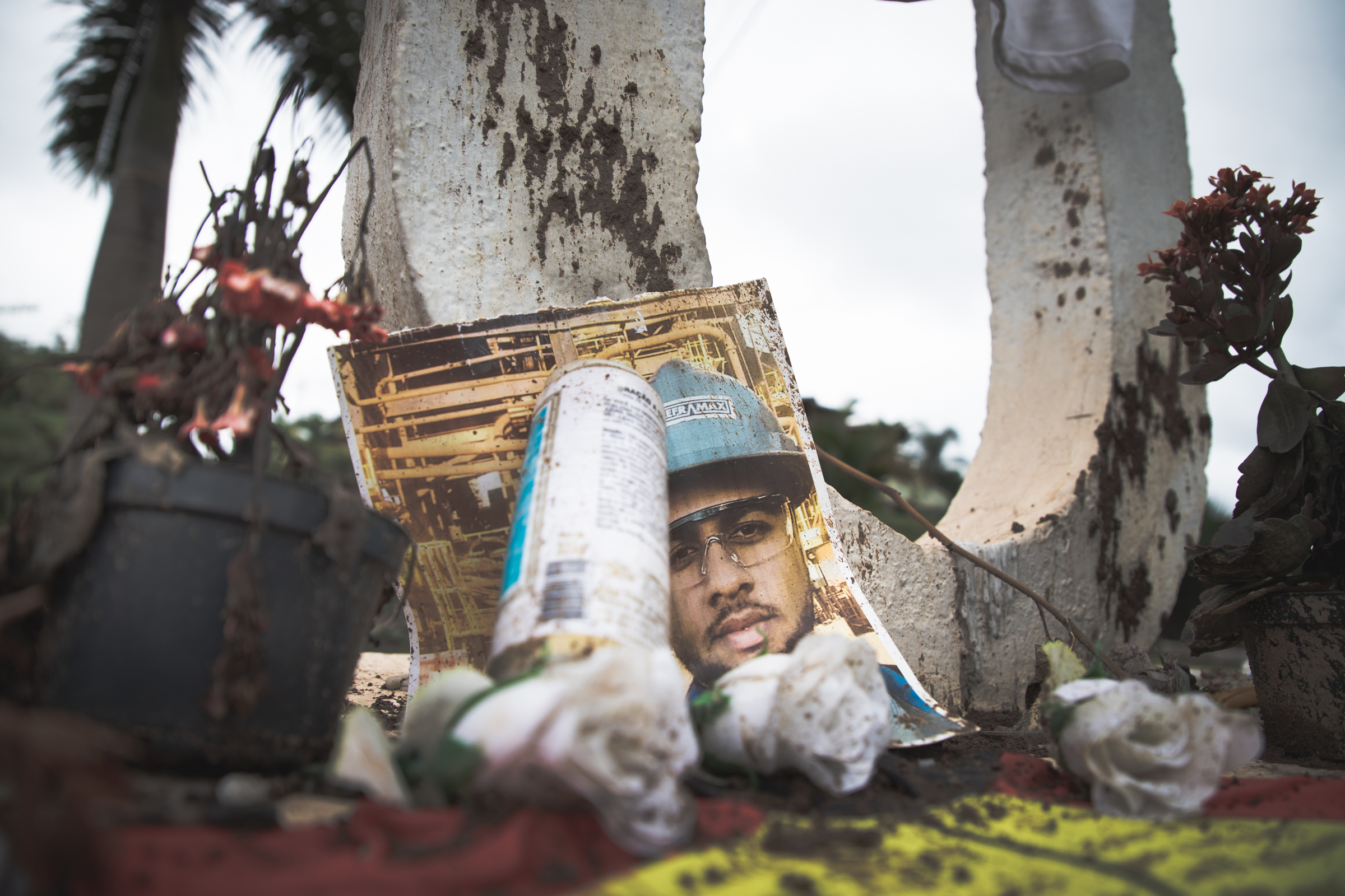 """The photograph of a worker killed in the Vale dam collapse of 2019 lies at the base of the of Brumadinho City sign in Minas Gerais. Alongside the photo, a hand-written sign states: """"Vale: lucro acima de tudo e lama acima de todos"""" (Vale: profit above everything and mud above all)."""