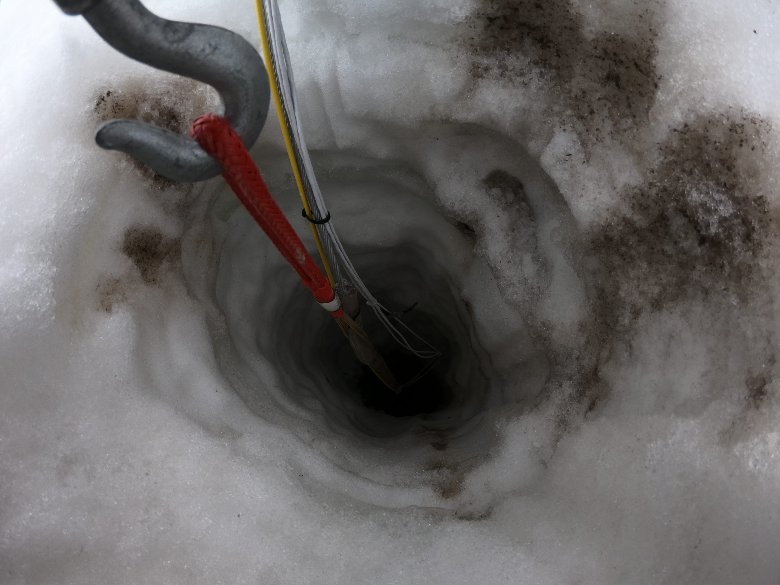 An eerie hole leads through 300 meters of ice, to a seafloor nearly half a mile below. A string of instruments was lowered through the hole and permanently frozen in, to monitor ocean currents, temperature, and melting on the underside of the ice shelf. Photograph by Douglas Fox