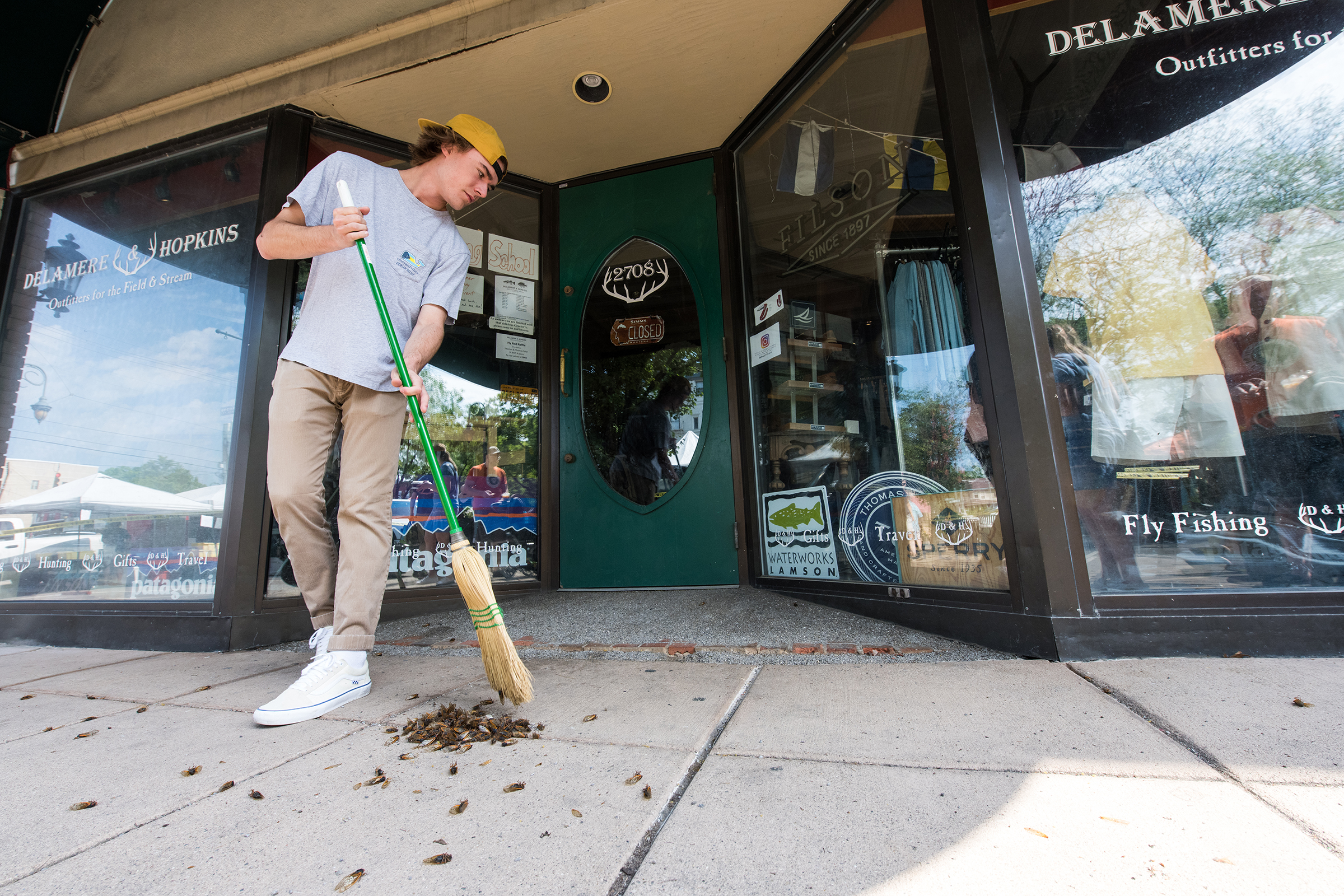 Jack Sullivan sweeps up a pile of Cicadas outside of a downtown Cincinnati, Ohio storefront in June of 2021.